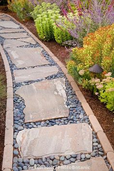 A pathway lined in brick with stepping stones and pebble filler