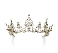 a beautiful diamond belle epoque tiara necklace, 1900. Featuring five large festoon motifs, with slightly smaller spacers, all linked by foliate scrolls, with a case stamped 'Goldsmiths and Silversmiths Company', it was sold at Sotheby's on 12 December 2013 for £67,300