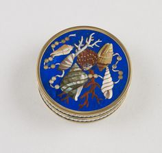 Italian Pietra dura circular box and cover. Cover and base decorated with arrangements of naturalistic shells in various colours and coral and ribbons threaded with pearls all on a lapis lazuli ground. Sides decorated with gold mounts in a chevron design.
