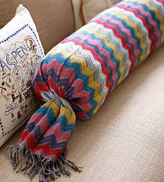 Cozy pillows are an easy way to update a space for winter. For this colorful bolster, sew two winter scarves into a long tube, stuff with batting, and secure the ends with rubber bands./
