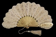 """""""Jenny Lind"""" fan  American or European, mid-19th century  Tan colored cloth decorated with sequins, carved and gilded wooden guards and sticks  Gift of Dr. Lotar and Luanna Stahlecker, KSUM 2004.31.18"""
