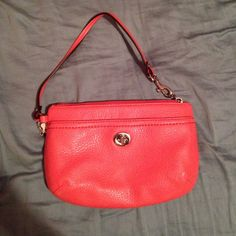 Coral medium coach wristlet Coral leather. Perfect condition; never used. Will fit an iPhone 5 & more. AUTHENTIC. Coach Bags Clutches & Wristlets