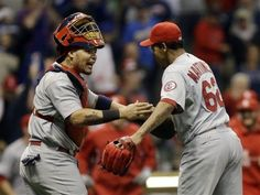 catcher Yadier Molina celebrates with relief pitcher Carlos Martinez after getting Milwaukee Brewers' Jeff Bianchi to ground out and end the 10th inning... Cards won the game 7-6.  9-20-13