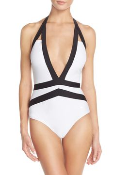 A deep front plunge spotlights a daring one-piece swimsuit from Ted Baker. It's also styled with cutout detailing and an adjustable halter neck.