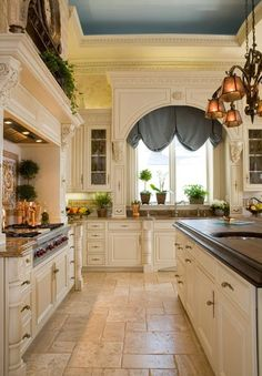Dutch Blue Ceiling and Shades offset by Cream and Yellow. Love the molding and glass cabinets.