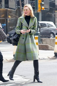Cate Blanchett in a green coat and black top and boots.