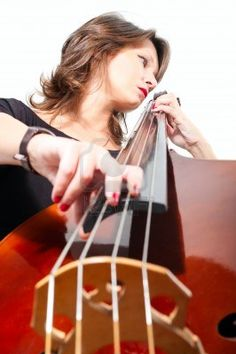 Young woman in black dress play double bass isolated on white  Low point view Stock Photo