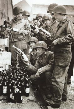 Liberation has its benefits for both liberators and liberated. Here, US troops liberate some fine French wine after entering a grateful French village, 1944.
