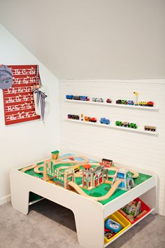 The home of photographer Carley Kay, as featured on 6th Street Design School.  Love the ledges above the train table.