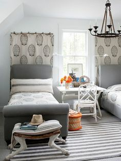 Neutral bedroom decor in shades of gray, white, and beige. The pattern in the fabric wall hangings and the mix of old and new furniture and accessories make this a really interesting room. Check out the legs on the bench!