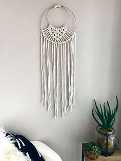Beautiful macrame piece hung by two silver rings. Looks beautiful in any space. +100% cotton rope +macrame detail +bohemian feel +natural color +dimensions approx : 10 by 18