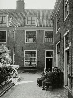 Buren / buurvrouwen /bewoners houden een praatje in het hofje bij het Proveniershuis (Proveniershofje) in Haarlem. [10 juli 1941].