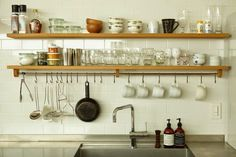 The Kobe kitchen has stainless steel counters, shelving with a built-in tool rail, and subway tiles.