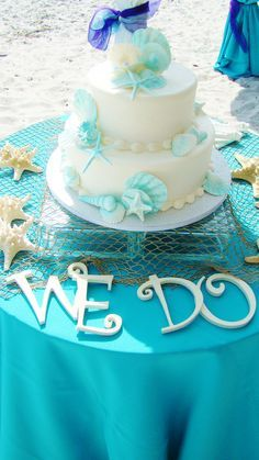 "Beach wedding cake with ""we Do"" saying."