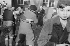 """Children wrestling outside a Jewish soup kitchen, Berlin. As a result of mounting antisemitism and wide-reaching Nazi racial policies, many middle-class German Jews became impoverished in the 1930s. By retaining aspects of middle-class life, Mittelstand Küchen helped them maintain their pride while benefiting from community assistance."" Roman Vishniac. Interwar period."