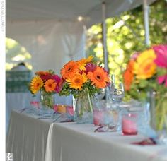 """Bright magenta, orange, and purple gerbera daisies –- Sean's favorite flower –- were showcased in rectangular glass vases for the table arrangements. """"They were so vivid, they really showed up beautifully against the white tent, especially after..."""