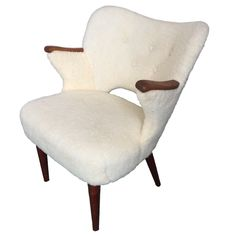 This vintage retro arm chair is newly upholstered in faux lambs wool. It stands on oak legs and has lovely teak nails.  Produced in Denmark in the 1950s, this unique chair is in great condition with minor signs of wear.  Dimensions in cm: H 83 x W 64 x D 68. Dimensions in inches: H 32.7 x W 25.2 x D 26.8.  For a quote on shipping, please inquire.