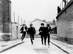 The Beatles run through the streets in 1964 during the filming of 'Hard Day's Night.'
