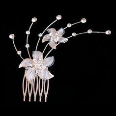 Luxe verzilverde en opvallende haarkam met 2 bloemen. De bloemen zijn voorzien van strass steentjes. De haarkam is erg fijntjes en gedetailleerd. Een lust voor het oog.  Onze haarkammen kunt u plaatsen in uw (opgestoken) haar. Door de aanwezige tandjes blijft deze zitten in uw haar. Wij adviseren de haarkam te gebruiken in opgestoken haar.  De haarkam is makkelijk zelf aan te brengen door de kam op de gewenste plek te plaatsen en aan te drukken.