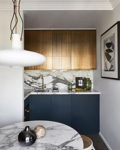 Small kitchen with dark blue lower cabinets and brass effect upper cabinet