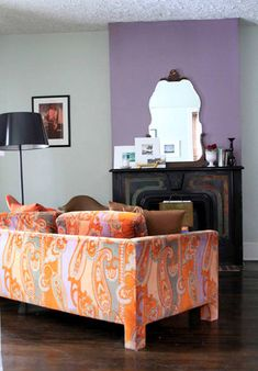 Loving this orange/gray/lavender together with the dark fireplace. Would kill for that couch.