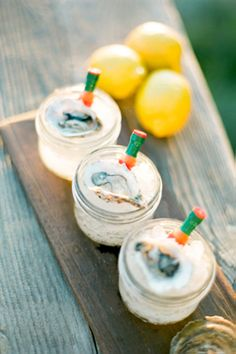 oyster shooters in individual mason jars with tiny tabasco bottles