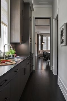 The butler's pantry in this luxurious Lincoln Park home features brushed absolute granite countertop and dark wood cabinets in Twilight to match those in the great room. #butlerspantry #moderndesign #urbanhome