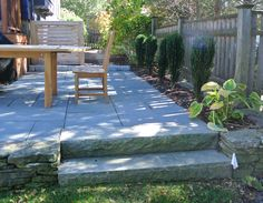 Granite step added for an easy transition from new bluestone patio to lawn