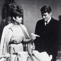"""The actress Audrey Hepburn photographed with the actor Peter O'Toole during an afternoon coffee at the Studio de Boulogne on a break in the filming of their movie """"How to Steal a Million"""". Paris (France), September 1965. Audrey was wearing: Trench coat: Burberry. Dress: Givenchy (of white wool, of his collection for the Autumn/Winter 1965/66). Belt: Givenchy (of black leather, of his collection for the Autumn/Winter 1965/66)."""