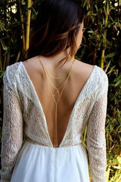 This cascading back necklace is a lovely piece of bridal jewelry that unites both gold and crystal elements, perfect for a backless wedding dress like this one. You'll see a small flash as the crystal nestled in the middle of the chain arrangement in the back as well as a similar one resting gently at the base of your neck.