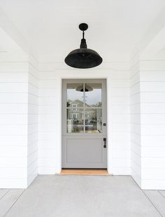Lovely cottage home features a white exterior accented with a gray front door illuminated by a vintage black barn pendant.