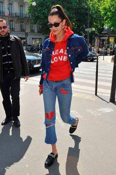 Bella Hadid usa calça cropped, jaqueta jeans, moletom vermelho e mule.