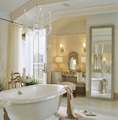 A sophisticated palette of white and beige gives this bathroom serenity and visual depth. Beams are painted a creamier shade of white than the ceiling to subtly distinguished one from the other. Small tiles zigzag across the floor and rectangular tiles are stacked vertically on the walls. For ultimate glamour, a glass chandelier hangs above the stand-alone tub.