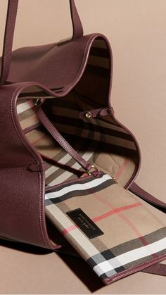 A softly structured Burberry tote bag in Mahogany Red and supple grainy leather. Spaciously sized, it is roomy enough to fit a tablet and beauty pouch inside, and contains a flying zip pocket for keeping essentials to hand.