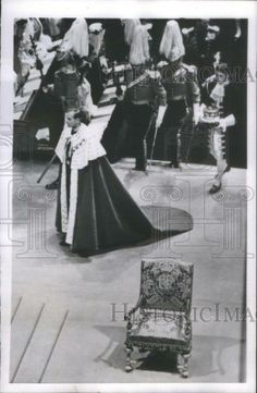 How to carry a robe; the Duke, followed by his page bearing his coronet, arrives for the Queen's coronation.