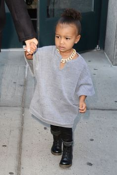 While in New York, the tot steps out in a Kanye-inspired look—an oversized gray sweatshirt and a gold chain.