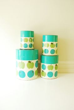Adorable 1950s 4 piece metal canister set with an apple & blueberry print. Perfect for your Retro kitchen! They are nesting style so they all