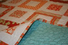 Orange quilt with teal flannel backing.