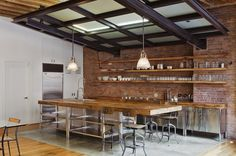 Commercial chic. Marrying the best of a commercial stainless steel kitchen with the warmth of wood, this space is both beautiful and functional. Industrial pendant lights, vintage Toledo chairs, open shelving and stainless steel cabinets topped with chunky wood workbenches are a perfect match against the exposed brick wall. Industrial Kitchen by Jane Kim Design   --Shared by WhatnotGems.Etsy.com Shop Etsy!
