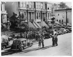 """A number of SF Japs crowd Bush St. sidewalk in preparation for their transfer to evacuation center for them at Tanforan -- Soldier escorts shown forground.""--caption on photograph :: Japanese American Relocation Digital Archive, 1941-1946"
