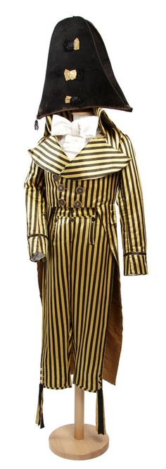 """Gentleman's """"Incroyable"""" style suit, late 1790s, of bright yellow and black striped silk satin ; comprising a dress coat with a high and firm collar, very wide revers, a double-breasted and straight-cut front with original painted copper buttons, long tails and shaped arms, lined in silk; the matching breeches with a fall-front, satin covered buttons and ribbons at the knees ; and an exaggerated bicorne hat of black silk plush, trimmed with three satin bows"""