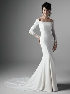 Admina Off-the-Shoulder Sheath Wedding Dress And voilà, the perfect fusion of elegance + glamour. This simple off-the-shoulder sheath wedding dress is designed for a sexy yet sophisticated statement. Talin stretch crepe Portrait off-the-shoulder neckline Beaded illusion long sleeves Lined with Brisa stretch jersey for comfort Zipper closure with pearl buttons trailing down to hemline Available in plus size Available in Sizes 0-28
