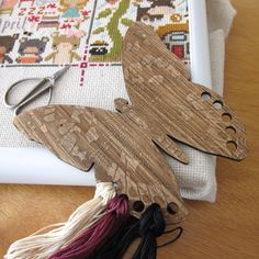 Embroidery floss holders help you stay organized while working on your next cross stitch, embroidery or needlepoint project. The Snuggly Monkey wooden Butterfly floss organizer includes a small roll o