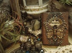 """""""I Believe"""" is a mixed media necklace which combines antique brass findings and filigrees, real brass chains, a beautifully antiqued brass butterfly, 18 gauge brass wires augmented by fire, faceted glass beads, ornate metal beads, Picasso Jasper, stained paper, stained lace and a handmade miniature leather cover book with coffee stained pages."""