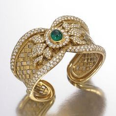 AN 18 KARAT GOLD, DIAMOND AND EMERALD CUFF BRACELET the hinged cuff set in the center with a cabochon emerald measuring approximately 9.9 by 8.0 mm., further set with round diamonds weighing approximately 13.95 carats, mounted in 18 karat white and yellow gold