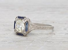 Art Deco vintage engagement ring made in platinum and centered with an approximatey 1.17 carat EGL certified old European cut diamond with I-J color and SI1 clarity. Accented with four calibre cut sapphires and four single cut diamonds. Circa 1920 Classic Art Deco styling melds perfectly with sapphire accents. Beautiful filigree makes this ring a unique and sweet example of Art Deco design. Diamond and gold mining has caused devastation in areas such as Africa, wreaking havoc on delicate…