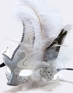 "White and silver Mardi Gras Masquerade Mask. White and peacock feathers and black silk ribbon ties. 6"" wide, 12"" tall"