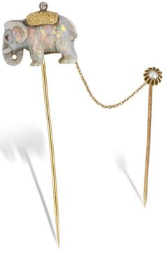A carved opal and gem-set double stick pin, circa 1900. The finely carved opal elephant, with ruby eyes and engraved gold and old brilliant-cut diamond howdah, connected to a half-pearl stick pin by a trace-link chain, pearl untested, lengths 7.6cm and 4.5cm. Via Bonhams.