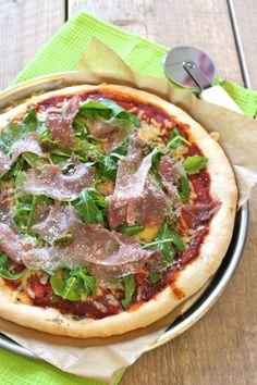 Italiaans pizza met parmaham, rucola en rode ui
