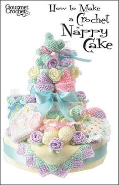 """Create a beautiful baby gift that doubles as the centerpiece for a baby shower. """"How to Make a Crochet Nappy Cake Pattern"""" has all the instructions needed to complete soft and cuddly crocheted toys, bib, booties, edgings, bottle covers and more. Combine these crochet baby accessories with purchased cloth and disposable diapers, called """"nappies"""" in Europe, to create a gorgeous tiered cake that will be the highlight of a shower."""